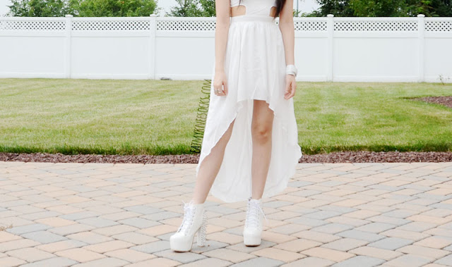 Get ready for summer with an all-white look, like this blend of edgy and bohemian, with a flowy high-low dress and spiked platform high-heel booties.