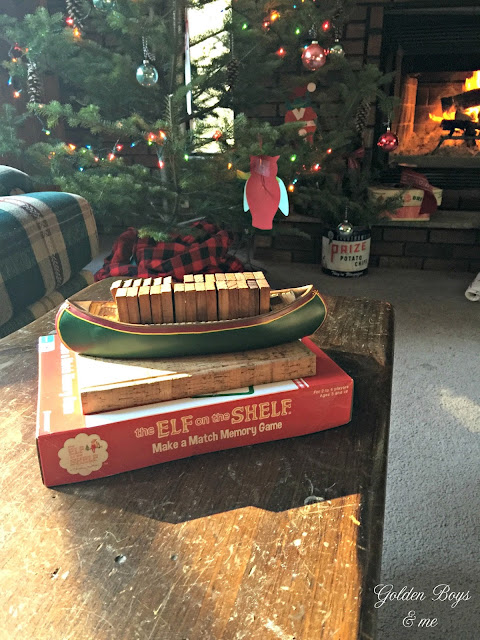 Elf on the Shelf memory game and canoe with dominos in cabin decorated for Christmas - www.goldenboysandme.com