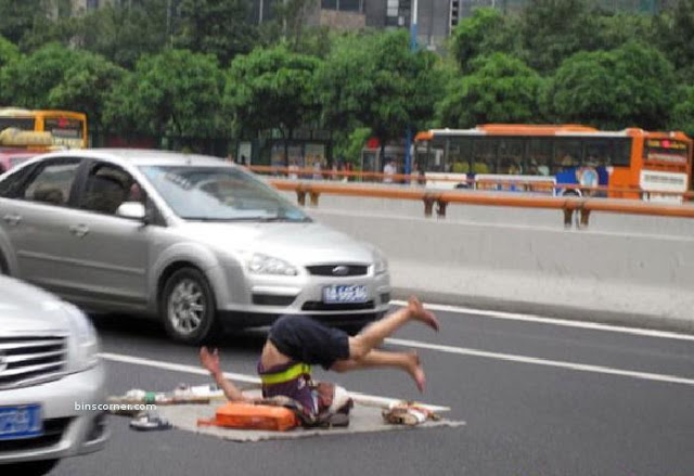 A man practises yoga in middle of a busy road