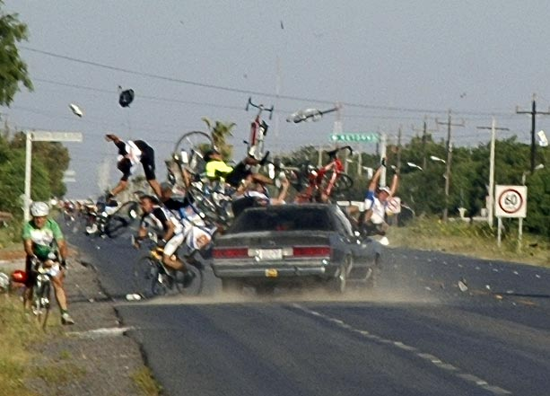 a large group of bicyclers are hurled from their bicycles as a large fast car crashes into them at high speed