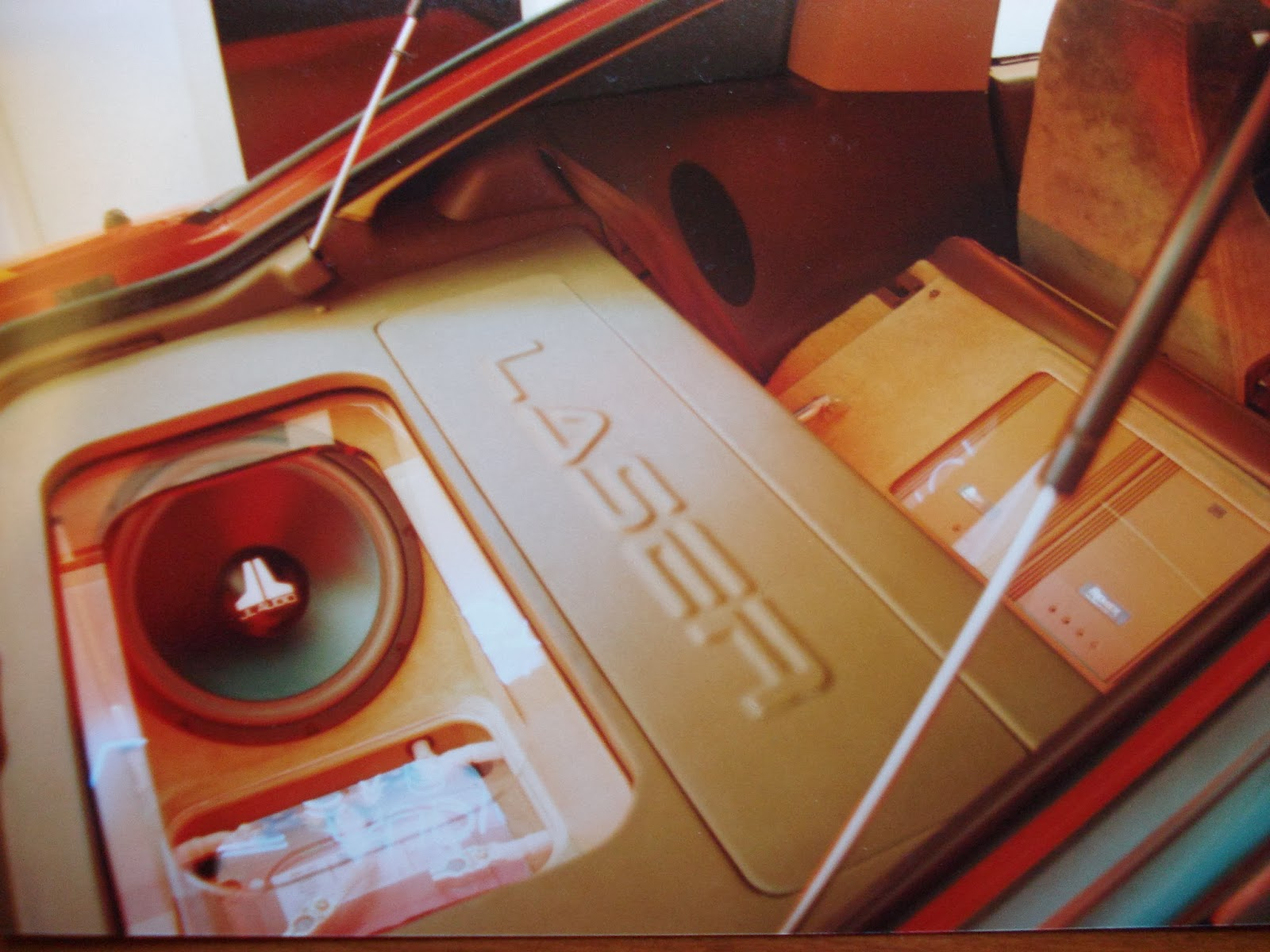 Photo image of the rear hatch area showing the woofer box, the battery rack, the motorized amplifier rack in the down position and the rear seat with the ODR system after being motorized open in Charles Barbosa's Red Laser as it stood during the winter storage at the end of 1995 and beginning of 1996.