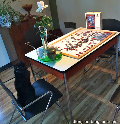Cat helping humans to work on a cat puzzle