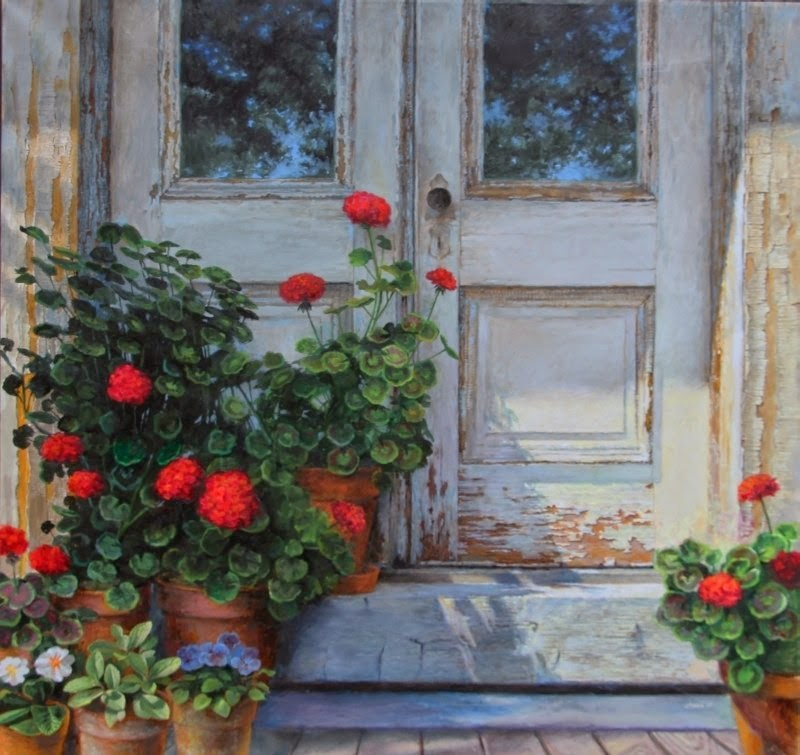 two worn doors, reflecting the sky and trees, with red geraniums at the base