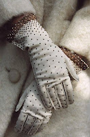 woman's crossed hands wearing old fashioned long white gloves