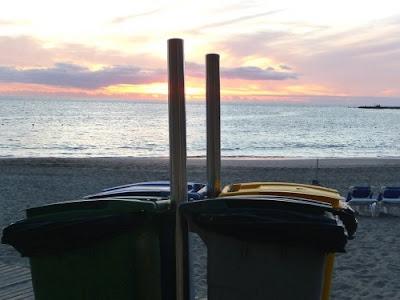 Cestini per la raccolta differenziata su una spiaggia al tramonto