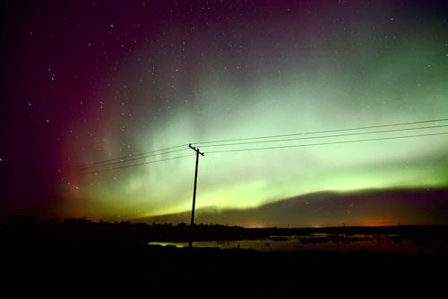 Solar aurora and power line (Credit: Pictureguy/Shutterstock.com ) Click to enlarge.
