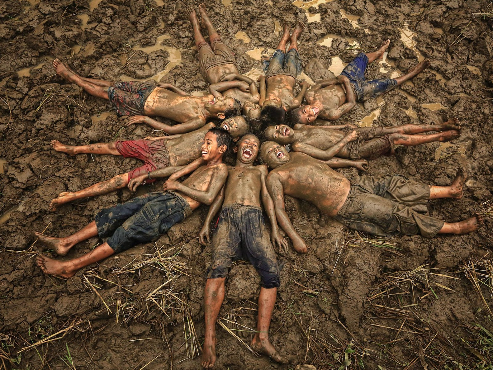 Children play in the mud after a football game in Indonesia