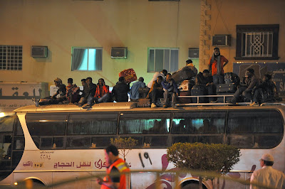Illegal migrants sit on the roof of a police bus with their belongings on November 13, 2013 before being transferred to a center in the capital Riyadh ahead of their deportation. Renewed clashes on November 13 between Saudis and illegal migrants, targeted in a nationwide campaign, killed one person and wounded 17. A Sudanese died as Saudis clashed with illegal migrants in the southern Riyadh neighborhood of Manfuhah, scene to riots over recent days. Last week, the ultra-conservative kingdom began rounding up thousands of illegals following the expiry on November 4 of a final amnesty for them to formalize their status.