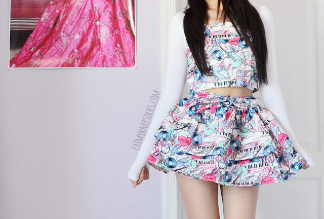 A cute, bubbly, Japanese Harajuku-inspired outfit, featuring a white long sleeve crop top and the pop art graffiti suspender top and flared skirt set from Romwe.