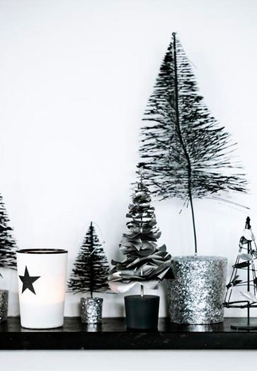 close up of black, white and silver line klein holiday display on a fireplace mantel with silver miniature christmas trees and candles