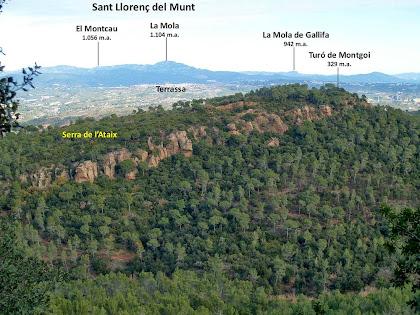 Panoràmica de la Serra de l'Ataix amb afloraments rocosos de gresos de color vermell. Al fons de tot sobresurt la Serralada de Sant Llorenç del Munt