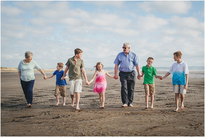 Children walking on the beach with grandparents