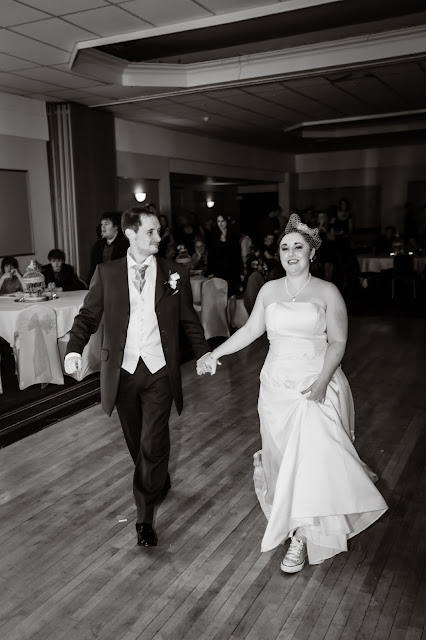 bride and groom on dance floor reading for first dance black & white photo