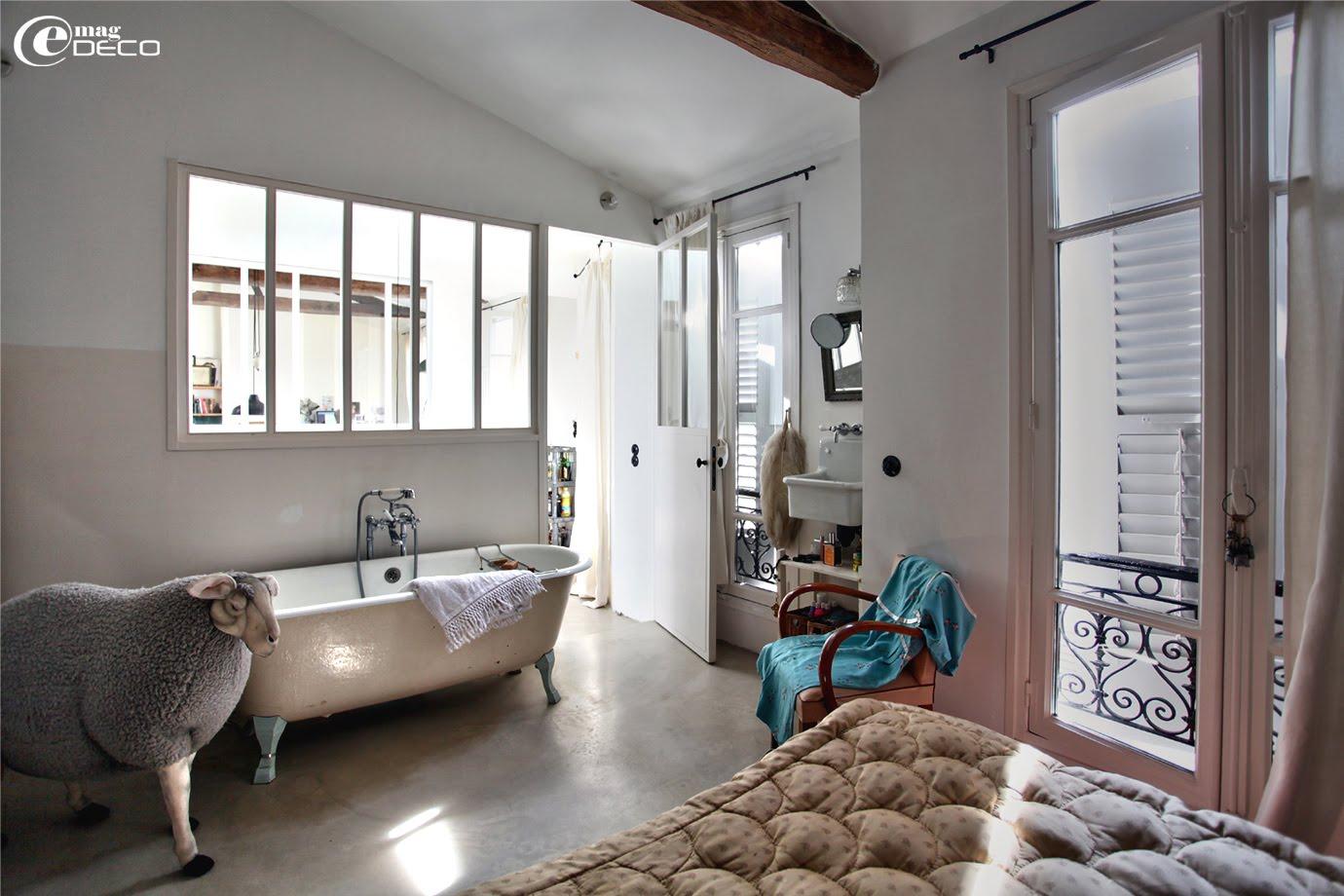 En face du lit, l'architecte d'intérieur Agathe Perroy met en scène une baignoire en fonte chinée