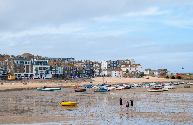St. Ives, boats and houses with people strolling along the beach west cornwall, england, UK