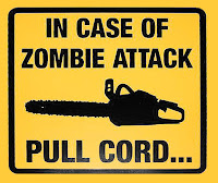 "Photo of yellow sign with legend ""In Case of Zombie Attack Pull Cord..."""