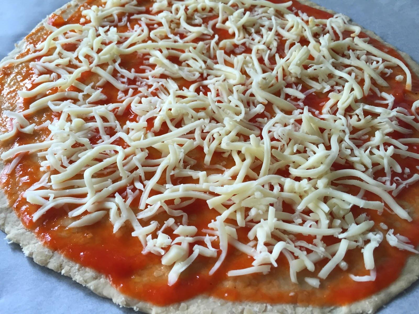 Pizza con chorizo y jalapeños. Poniendo la base de tomate y mozzarella.