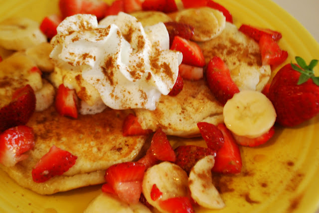 Delicious yogurt pancakes with strawberries, bananas, syrup, whipped cream, and cinnamon