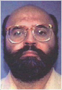 Interpol mug shot of a balding, middle-aged man of Indian ethnicity. He has a fringe of black hair and a full black beard and mustache and is wearing oversized 1980s style glasses.