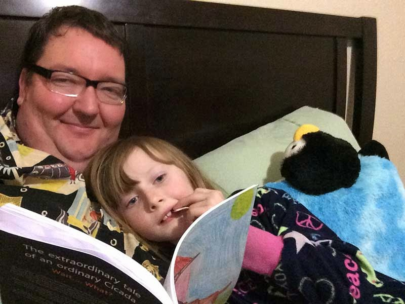 big guy with glasses reads a book to his daughter