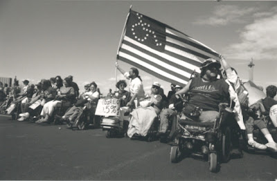 Protestors - many using wheelchairs and one man with an american flag that has the stars in the shape of a wheelchair