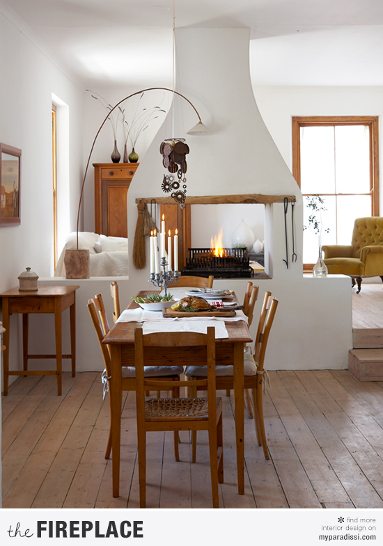 A country style central two-sided fireplace serving as a room divider ©Greg Cox via House and Leisure