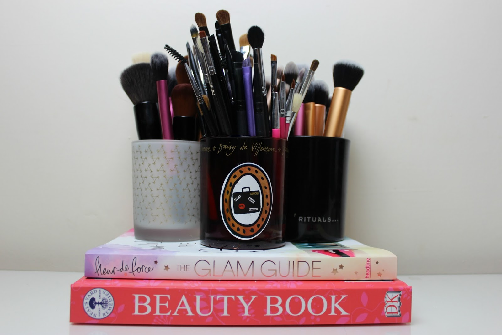 A picture of makeup brushes, candles and beauty books