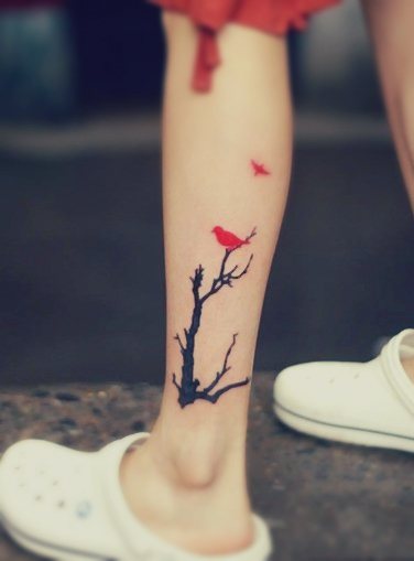 A tattoo featuring a red bird resting on a black tree and another bird flying away
