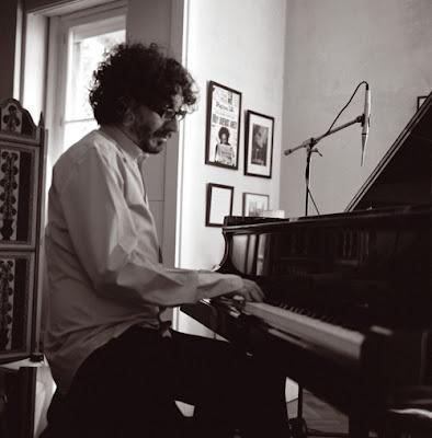 Foto em preto e branco mostra Fito Paez tocando um piano em uma pequena sala, com fotos emolduradas na parede, ao fundo.