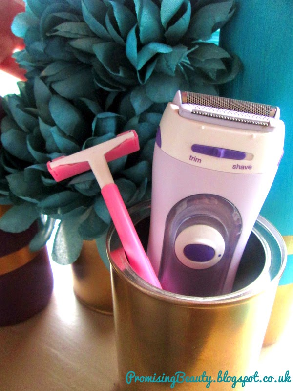 Braun electic shaver and bic lady razor in gold pot with teal flowers behind. Causes of shaving irritation, itching and red bumps.