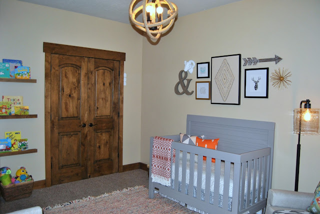 nursery, boy nursery, gender neutral nursery, child, children, bedroom, baby room, orange, curtain, reclaimed wood, rustic, rustic nursery, rope light, chandelier, edison bulb, pouf, rocker, rocking chair, modern, gray crib, gallery wall, faux taxidermy, burlap, bench, storage bench, faux fur rug