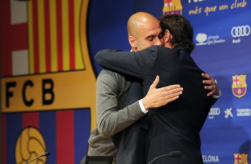 Barcelona president Sandro Rosell hugs departing coach Pep Guardiola