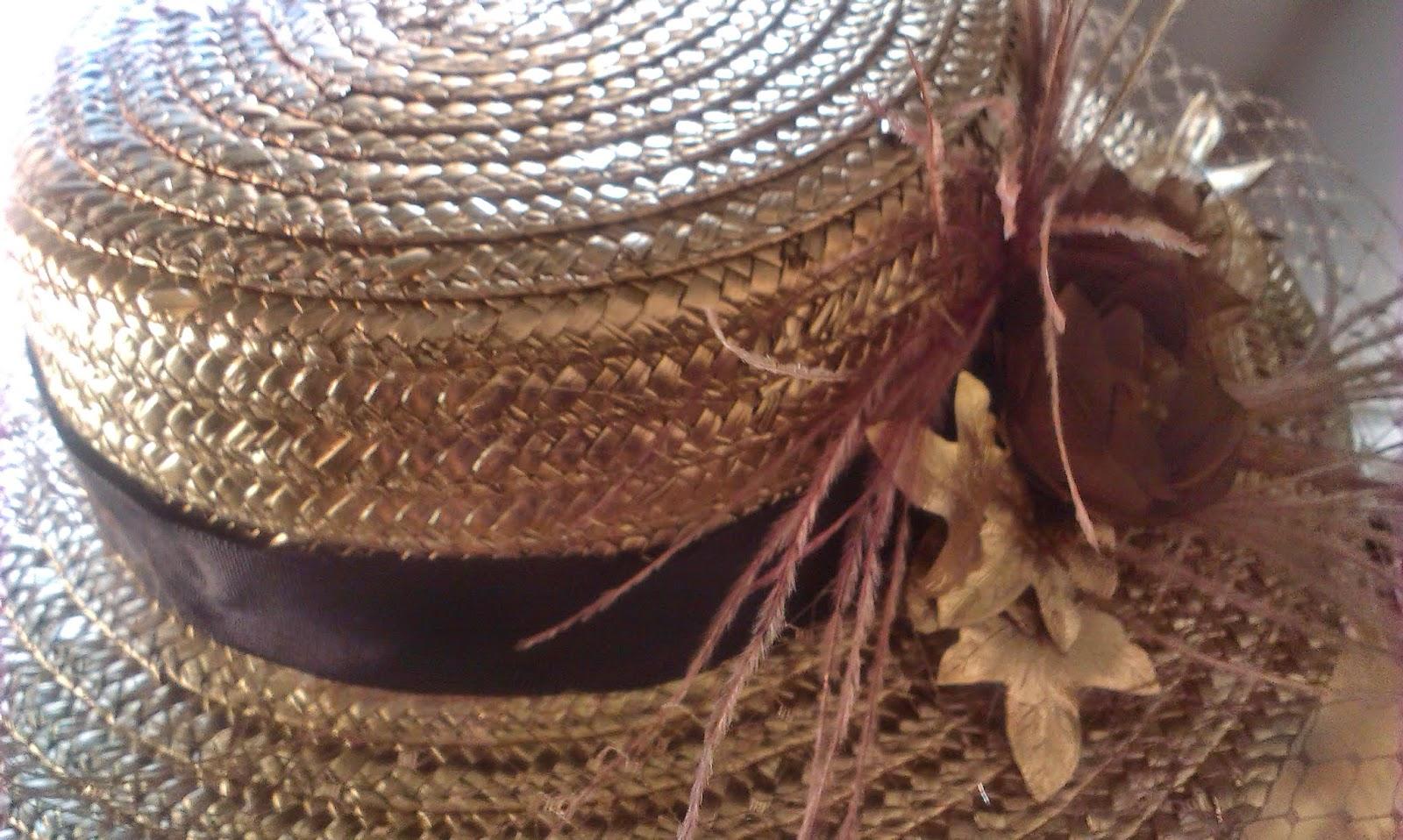 Canotier dorado de copa baja con velo, cinta grossgrain color chocolate, decorado con plumas de avestruz, flores hechas a mano y hojas de eucalipto doradas