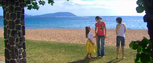 Mikami and Lisa are approached by one of the children on a beautiful beach.