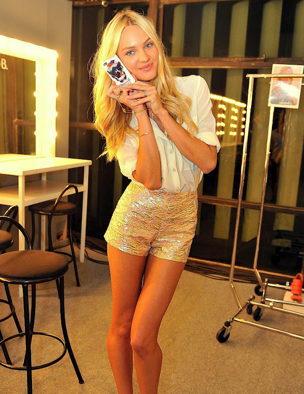 Candice Swanepoel in short gold shorts in a dressing room