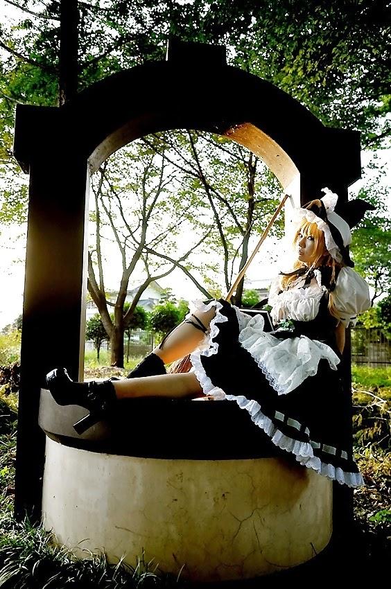 jeune femme asiatique cosplayé en gouvernante assise sur un puits