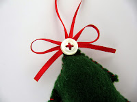 Sewing a button to a felt Christmas tree decoration