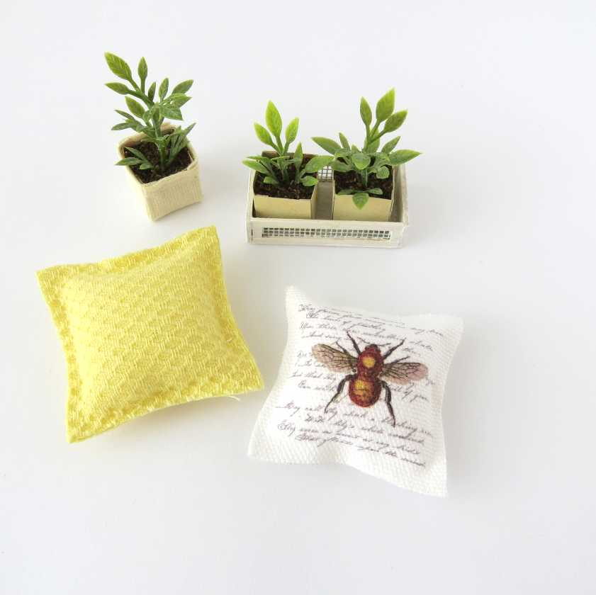 Piante finte e cuscini a tema ape in miniatura