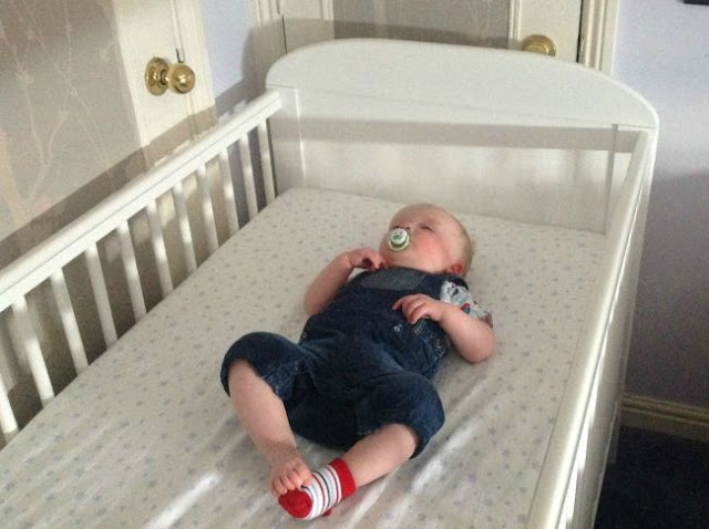 baby asleep on back in white cot