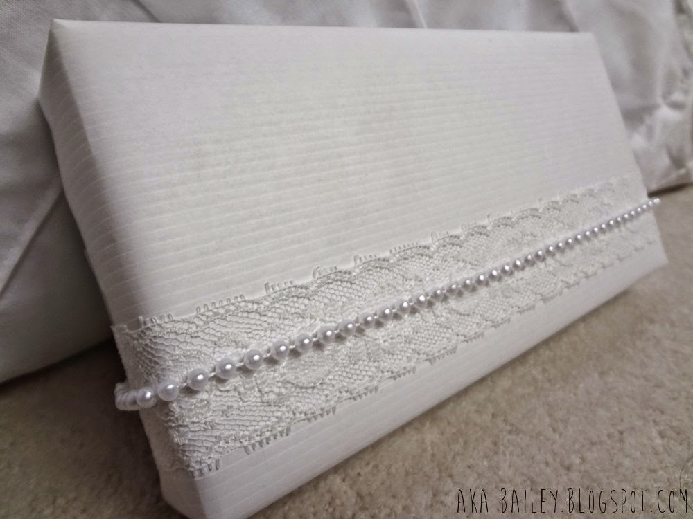 White paper gift wrap, white lace, and white pearls