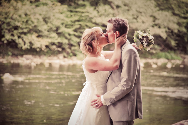 A bride and groom in front of a river