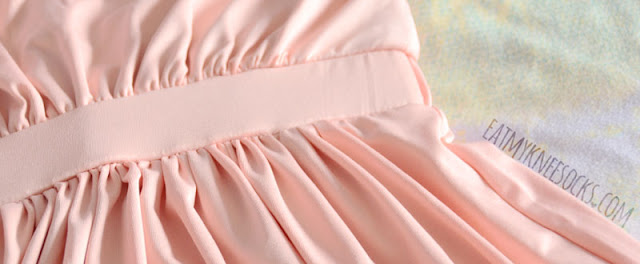 Close-up on the elastic waistband and ruched detailing on the pink WalkTrendy halter dress.
