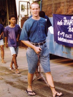 Martin Garnett is led away in chains after his arrest in Thailand in 1993.