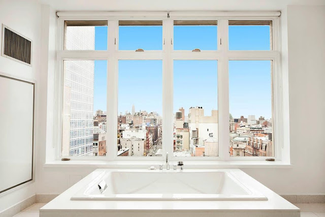 Bathtub in the bathroom of a NYC penthouse with a view of NYC