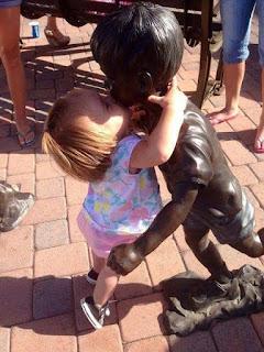 Cute Girl kissing a statue