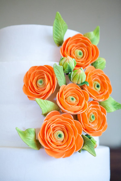 Bright Orange Flowers Beautiful wedding cake set over four round tiers in