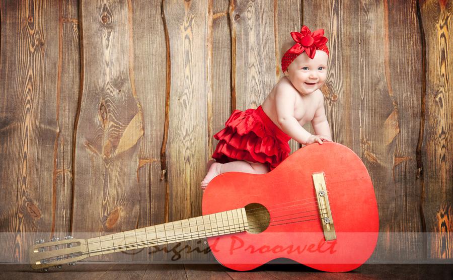 tüdruk punases fotostuudios punane kitarr-pildistamine