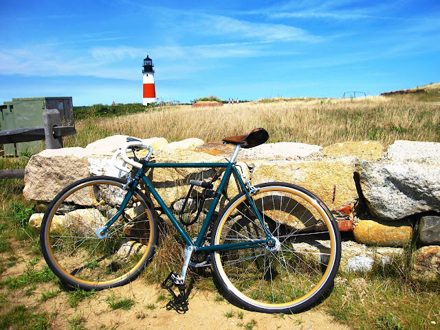 A bike, a rock wall, and a lighthouse in Nantucket