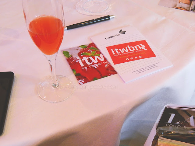 a red cocktail and a cards on a white table