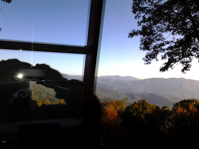 on a 40 foot extension ladder, the reflection of valleys spills away below Little Switzerland, NC